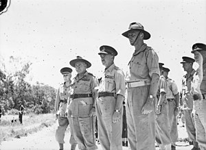 A group of soldiers in shirt sleeves stand at attention.