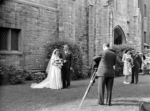 Wedding photography - A newlywed couple standing in front of a church and their wedding photographer, Westmount, Montreal, 1945