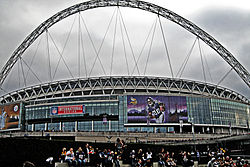 Wembley Stadium from the outside featuring a football player on a screen