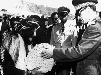 Land reforms by country - photo of the Shah distributing land deeds during Iran's White Revolution