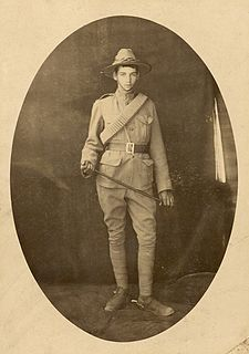 Full-length studio portrait of a young man in khaki military uniform. He has a broad brim hat on, and is holding a riding crop.