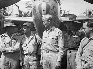 Five men in uniform stand in front of a dual propeller aircraft.