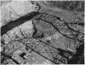 """""""View east from the downstream trestle showing a portion of a fault zone east of section 30 on the left. The grizzly... - NARA - 294260.tif"""