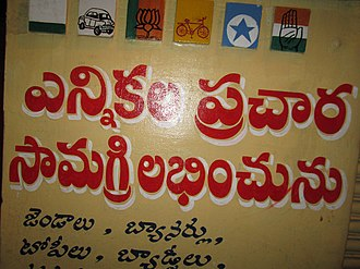 Wall painting at a shop in India. It first shows the painted party symbols of all the major political parties in the region during the nationwide elections in India in 2014. It also has a Telugu inscription showing availability of political flags, banners, caps, badges and other election material. ennikl prcaar saamgri dukaannmu.jpg