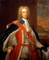A three-quarter portrait of a man wearing 18th-century dress. He wears a white frock, under a red coat, topped by a blue gown. He wears a large gold chain around his neck, which descends as far as his chest. He has a long white wig, and behind him a portrait of a shoreline is visible.