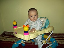 A six month old child sitting in a baby walker, 2012.