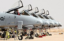 Side view of five jet aircraft with canopies opened parked side-by side.