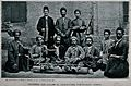 A group of men are sitting on the ground bound together by c Wellcome V0041219.jpg