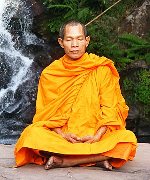 Meditation - Buddhist monk meditating in a waterfall setting