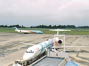 Japan Air System - A Japan Air System MD90 with an Akira Kurosawa paint scheme, with another JAS MD-90 (wearing another livery) in the background