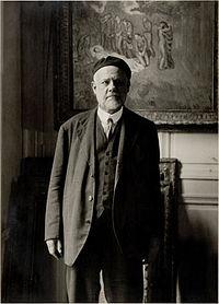 Fotografia di Ambroise Vollard, sullo sfondo si intravede l'opera Evocación, realizzata da Picasso nel 1901