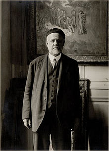 Ambroise Vollard, starante antaŭ Evocación de Picasso. El-entiero de Casagemas.jpg