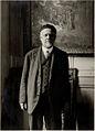 Ambroise Vollard, standing in front of Picasso's Evocación. El entierro de Casagemas.jpg