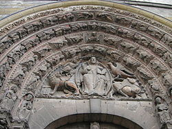 The sculptured section from above a Gothic door. The pointed archway has four molded bands carved with small angels. The triangular section framed by the arch has the figure of Christ surrounded by the Four Heavenly Beasts, the eagle of St John, the winged ox of St Luke, the winged man of St Matthew and the winged lion of St Mark.