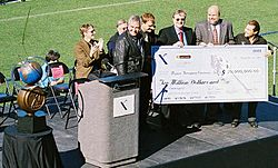 Paul Allen (in sun glasses and crimson tie) and Burt Rutan (leather jacket) were presented with the Ansari X PRIZE by members of the X PRIZE Foundation in 2004.