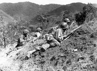 Battle of Luzon - A squad leader points out a suspected Japanese position at edge of Baleta Pass, near Baguio, where troops of the 25th Inf. Div. are in fierce combat with the enemy. 23 March 1945.