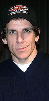 Stiller is facing the camera and smiling. He is wearing a baseball cap and a blue shirt with a white T-shirt underneath.
