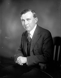 Black and white portrait of a man in a suit sitting in a chair.