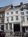 foto van Huis, waarvan de gevel in de trant der zgn. Maaslandse renaissance eindigt in een hoofdgestel met consoles. Gevelsteen IN DEN LUYPAERD, afkomstig van Vrijthof 9.