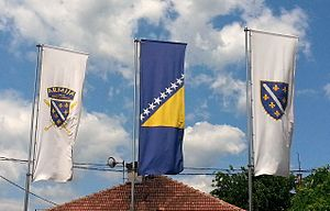 Flag of Bosnia and Herzegovina - Current and old flags of Bosnia and Herzegovina, along with that of the army flying in front of the grave of Alija Izetbegović.