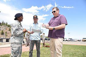 Broken Lizard - Kevin Heffernan (right) and Steve Lemme (center) of Broken Lizard sign an autograph during a visit to Cheyenne Mountain Air Force Station in 2016.