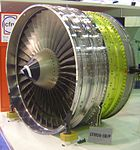 The front fan of a jet engine facing the left of the image, surrounded by its metal casing. The conical inlet in seen right in front of the metal fan blades. The fan casing is seen in three distinct (but attached) sections from left to right, first a silver-colored section, then a golden-colored section, then another silver-colored section.