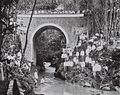 COLLECTIE TROPENMUSEUM Een Europees gezin poseert met een grote groep Javanen bij een boogbrug over een rivier bij de dessa Wanasigra in de onderdistrict Tjikoneng. TMnr 60042298.jpg