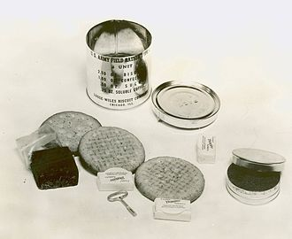 C-ration - An opened 1941 B unit with contents: cellophane wrapped chocolate fudge, 3 biscuits, 3 pressed sugar cubes, small tin of soluble (instant) coffee