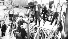 DeMille on a stand, holding a megaphone, giving commands to crew members which surround him and several film cameras