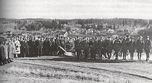 A crowd of men gathered in a field watching one man push a plow