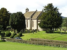 grey stone building set in background with green fields and graveyard in foreground