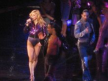 A female blond performer singing in a purple leotard and high heeled shoes. She is singing while looking to the right while on her left, a group of dancers in violet colored clothes strike different poses.