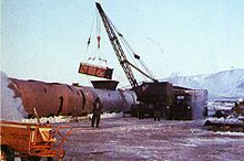 A crane shown loading contaminated ice into a large steel tank.