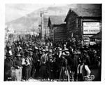 Crowd of people waiting for mail at Dawson Post Office, showing log buildings and sign for mine broker's office, ca 1898 (NOWELL 30).jpeg