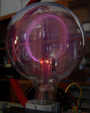 Cathode ray - A beam of cathode rays in a vacuum tube bent into a circle by a magnetic field generated by a Helmholtz coil.   Cathode rays are normally invisible; in this tube enough residual gas has been left that the gas atoms glow from fluorescence when struck by the fast moving electrons.