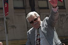 Caucasian man with white hair and mustache raising his left arm.  He is wearing sunglasses, a jacket and tie.