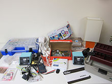 Small electronics tools and supplies arranged on a table against a white wall