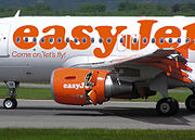 "The middle of an airplane fuselage, white with ""easyJet"" painted in orange, is visible with the jet engine under the wing in the center of the image. Small doors on the rear half engine are open"