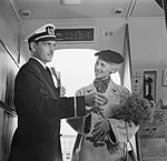 Een KLM-purser verwelkomt een reiziger in de cabine en duidt haar de ziplaats, Bestanddeelnr 252-1234.jpg