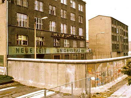 The top of the Wall was lined with a smooth pipe, intended to make it more difficult to scale. The areas just outside the wall, including the sidewalk, are de jure Eastern Bloc territory. 1984. Exterior of East Berlin Neue Zeit newspaper, with Berlin Wall in foreground.jpg