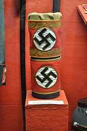 Two red armbands bearing swastikas, mounted on a stand