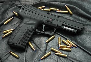 Photo of an all-black Five-seven USG pistol surrounded by 5.7×28mm