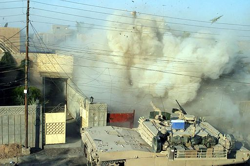 US Marine Corps tank taking part in the Rape of Fallujah (Iraq, 2004). Public Domain.