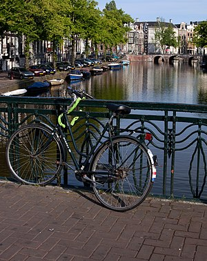 A bicycle with the Dutch flag parked on a bridge across one of Amsterdam's many canals.
