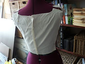 Pattern (sewing) - Fitting a muslin on a dress form. This dress form is adjustable to match the wearer's unique measurements, and the muslin is fit around the form accordingly, by taking it in or letting it out, a smaller or larger fit can be made from the original pattern.