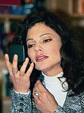 Fran Drescher applying make-up while looking in a compact mirror