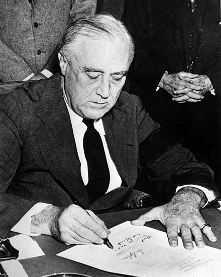 President Roosevelt, wearing a black armband, signs the Declaration of War on Japan on December 8, 1941 Franklin Roosevelt signing declaration of war against Japan.jpg