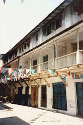Grande maison en longueur d'aspect vétuste, avec des murs blancs, deux étages, de nombreux balcons et fenêtres.