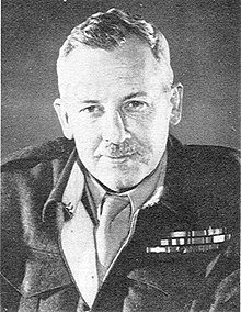 Head and shoulders of man with a moustache wearing battledress jacket and ribbons with a shirt and tie.