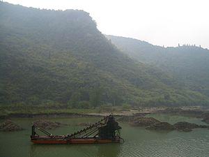 Jiugong Mountains - The Jiugong mountains rising over a reservoir on the Fushui River